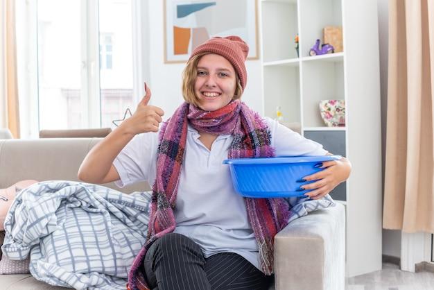 Нездоровая молодая женщина в теплой шляпе с шарфом на шее, держащая тазик, чувствуя тошноту, улыбается, показывает палец вверх, чувствуя себя лучше, сидя на диване в светлой гостиной