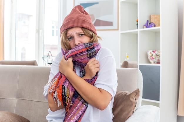 Нездоровая молодая женщина в теплой шляпе с шарфом на шее, чувствуя себя нездоровой и больной, страдающая от простуды и гриппа, беспокоится, сидя на диване в светлой гостиной