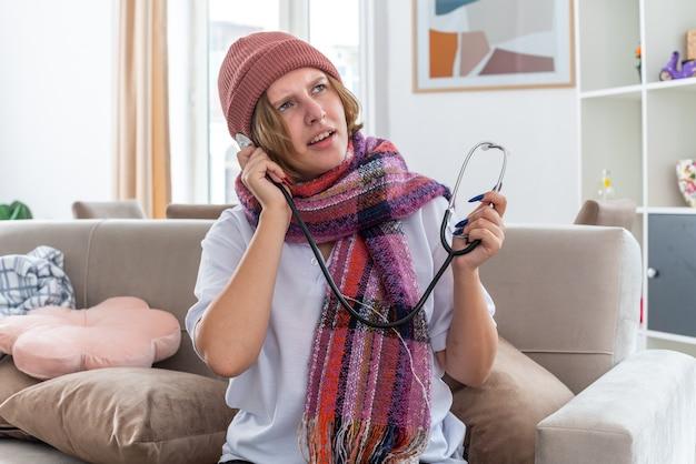Нездоровая молодая женщина в теплой шляпе с шарфом на шее, держащая стетоскоп, чувствует себя нездоровой и больной, страдает от простуды и гриппа, выглядит обеспокоенной, сидя на диване в светлой гостиной