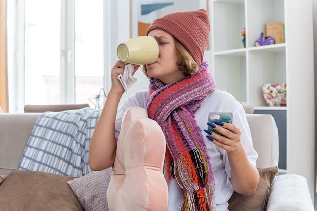 가벼운 거실의 의자에 앉아 감기와 독감으로 더 나은 고통을 받기 위해 따뜻한 차를 마시고 아프고 아픈 컵을 마시는 스카프와 따뜻한 모자에 건강에 해로운 젊은 여성