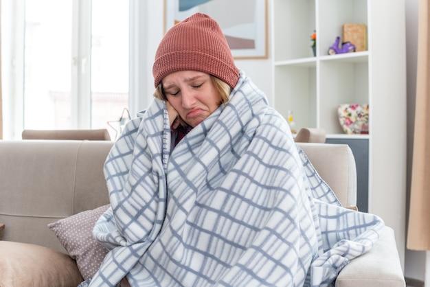 따뜻한 모자에 건강에 해로운 젊은 여성이 담요에 싸여 감기와 독감으로 고통을 겪고 가벼운 거실에서 소파에 앉아 발열과 두통을 앓고 있습니다.