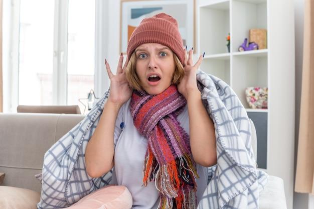 따뜻한 모자에 건강에 해로운 젊은 여성이 담요에 싸여 감기와 독감으로 고통 받고 온도계가 발열이 걱정되고 가벼운 거실에서 소파에 앉아 무서워 보입니다.