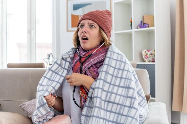 따뜻한 모자에 건강에 해로운 젊은 여성이 담요에 싸여 감기에 걸려 몸이 좋지 않고 아픈 고통을 겪습니다.