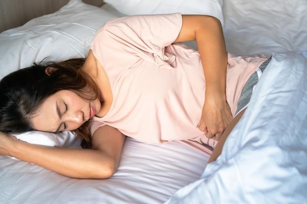 Нездоровая молодая женщина лежит на кровати и держится за живот, чувствуя дискомфорт и страдает от боли в животе