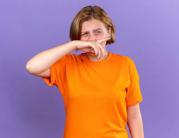 Giovane donna malsana in maglietta arancione che si sente terribile asciugandosi il naso con la mano che soffre di naso che cola con espressione triste in piedi sul muro viola