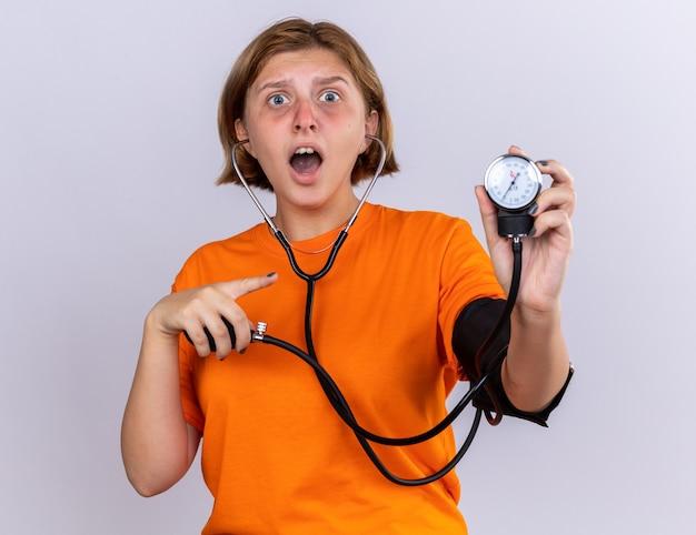 Giovane donna malsana in maglietta arancione che si sente male misurando la pressione sanguigna usando il tonometro che sembra preoccupata in piedi sul muro bianco