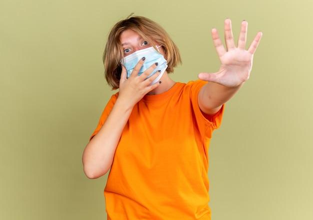 Giovane donna malsana in t-shirt arancione che indossa una maschera protettiva facciale sensazione di malessere che soffre di virus che fa un gesto di arresto con la mano che sembra preoccupata in piedi sul muro verde