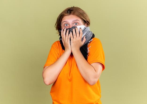 Giovane donna malsana in maglietta arancione che indossa una maschera protettiva per il viso con una sciarpa calda intorno al collo e al viso che si sente male soffre di freddo e sembra preoccupata in piedi sul muro verde