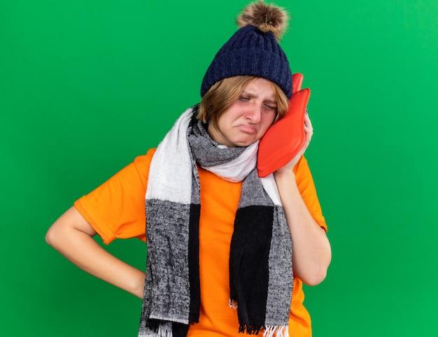 Giovane donna malsana in t-shirt arancione con cappello e sciarpa calda intorno al collo sensazione terribile con in mano una borsa dell'acqua calda che soffre di espressione fredda e triste