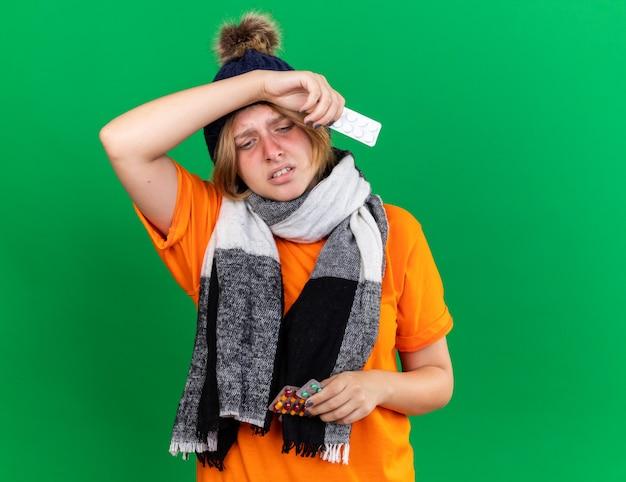 Giovane donna malsana in t-shirt arancione con cappello e sciarpa calda intorno al collo sentendosi terribili in possesso di pillole che soffrono di virus con febbre in piedi sul muro verde