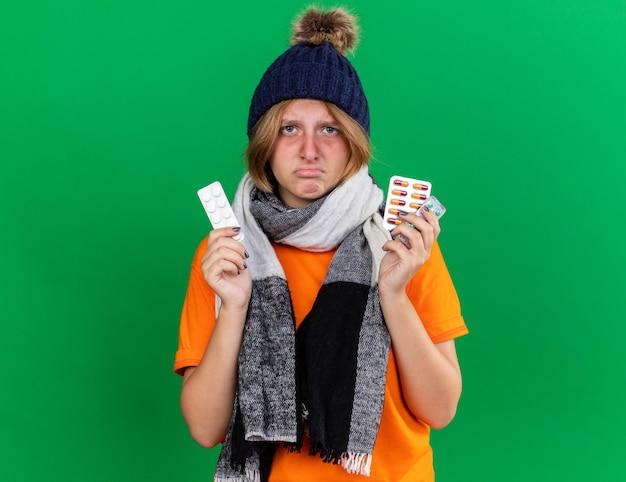 Giovane donna malsana in t-shirt arancione con cappello e sciarpa calda intorno al collo che si sente terribilmente in possesso di pillole che soffrono di virus in piedi sul muro verde