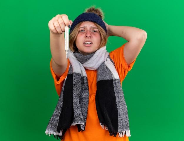 Giovane donna malsana in maglietta arancione con cappello e sciarpa calda intorno al collo che si sente terribilmente tenendo il termometro con la febbre che soffre di influenza