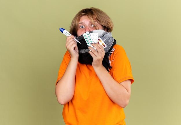 Giovane donna malsana in t-shirt arancione con sciarpa calda intorno al collo e al viso che si sente male soffrendo per il freddo che tiene pillole e termometro che sembra preoccupato