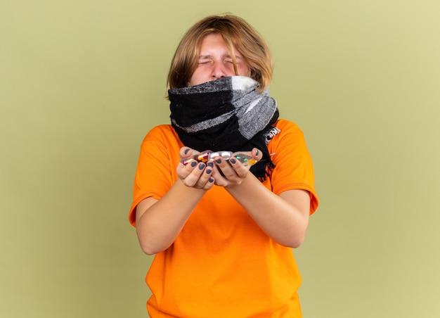 Giovane donna malsana in t-shirt arancione con sciarpa calda intorno al collo sentendosi terribilmente sofferente di influenza in possesso di diverse pillole che sembra delusa in piedi sul muro verde