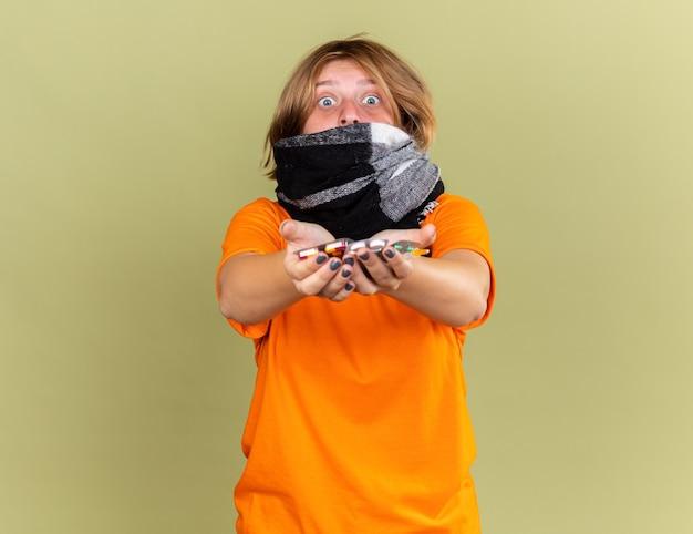 Giovane donna malsana in t-shirt arancione con sciarpa calda intorno al collo sentendosi terribilmente sofferente di influenza in possesso di diverse pillole che sembra preoccupata in piedi sul muro verde