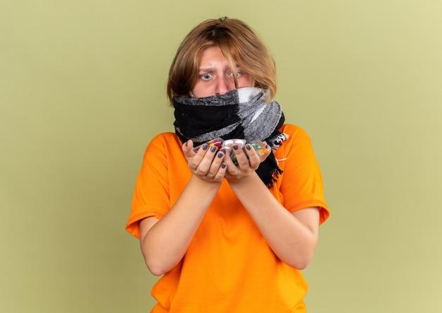 Giovane donna malsana in t-shirt arancione con sciarpa calda intorno al collo sentendosi terribilmente sofferente di influenza con in mano diverse pillole che sembrano preoccupate