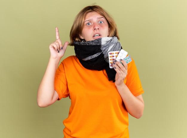 Giovane donna malsana in t-shirt arancione con sciarpa calda intorno al collo sensazione di malessere che soffre di influenza in possesso di diverse pillole che sembra confusa mostrando il dito indice in piedi sul muro verde