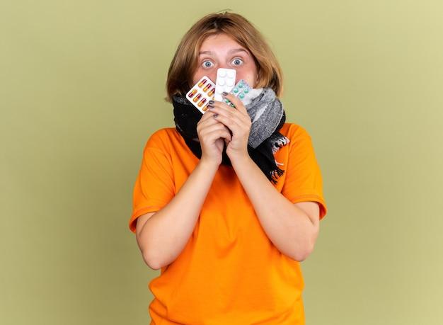 Giovane donna malsana in t-shirt arancione con sciarpa calda intorno al collo sensazione di malessere che soffre di influenza in possesso di diverse pillole che sembra confusa e preoccupata in piedi sul muro verde