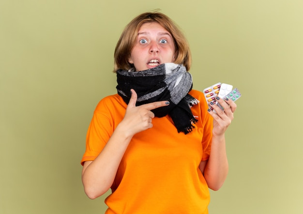 Giovane donna malsana in t-shirt arancione con sciarpa calda intorno al collo sensazione di malessere che soffre di influenza in possesso di diverse pillole che sembrano confuse