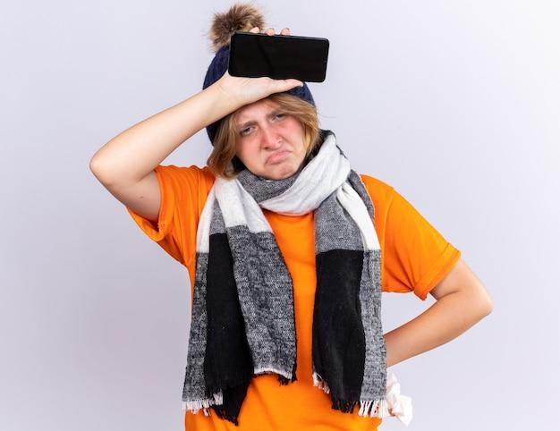 Giovane donna malsana in maglietta arancione con sciarpa calda intorno al collo e cappello che si sente terribile tenendo lo smartphone e il tessuto che soffrono di raffreddore e influenza che sembrano delusi sul muro bianco