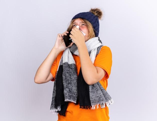 Giovane donna malsana in t-shirt arancione con sciarpa calda intorno al collo e cappello che si sente terribilmente parlando al cellulare che soffia il naso che cola starnutisce nel tessuto