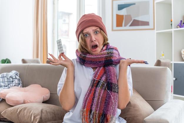 Giovane donna malsana in cappello caldo con sciarpa intorno al collo che tiene malessere e malato soffre di raffreddore e influenza tenendo pillole allargando le braccia ai lati seduta sul divano in un soggiorno luminoso