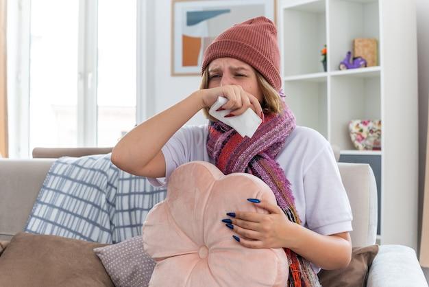 Giovane donna malsana in cappello caldo con sciarpa che soffia il naso nel tessuto starnuti soffrendo di raffreddore e influenza seduta sulla sedia in soggiorno luminoso