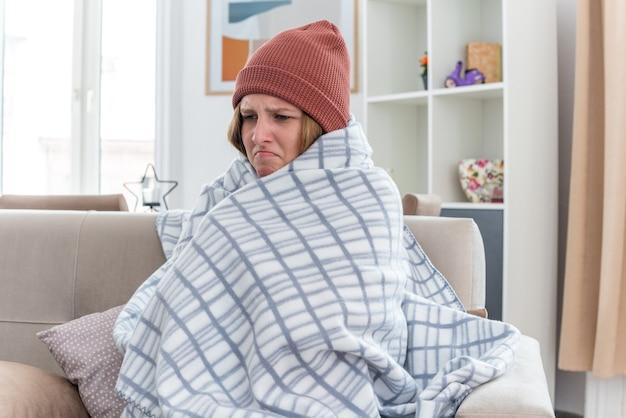 Giovane donna malsana con un cappello caldo avvolto in una coperta che sembra malata e malata che soffre di raffreddore e influenza con febbre e mal di testa seduta sul divano in un soggiorno luminoso