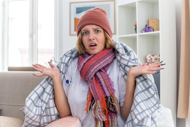 Giovane donna malsana con un cappello caldo avvolto in una coperta che sembra malata e malata che soffre di raffreddore e influenza con termometro che ha la febbre che sembra confusa seduta sul divano in un soggiorno luminoso