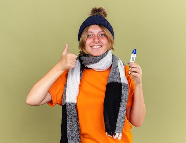 Нездоровая молодая женщина в шляпе с шарфом на шее чувствует себя лучше, держа цифровой термометр, улыбаясь, показывая пальцы вверх, стоя над зеленой стеной