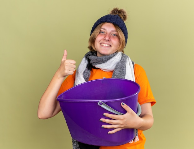 Unhealthy young woman wearing hat with scarf around her neck feeling better suffering from nausea holding basin showing thumbs up smiling