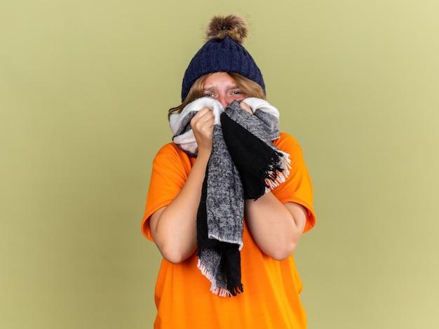 Нездоровая молодая женщина в шляпе с шарфом на шее ужасно страдает от гриппа