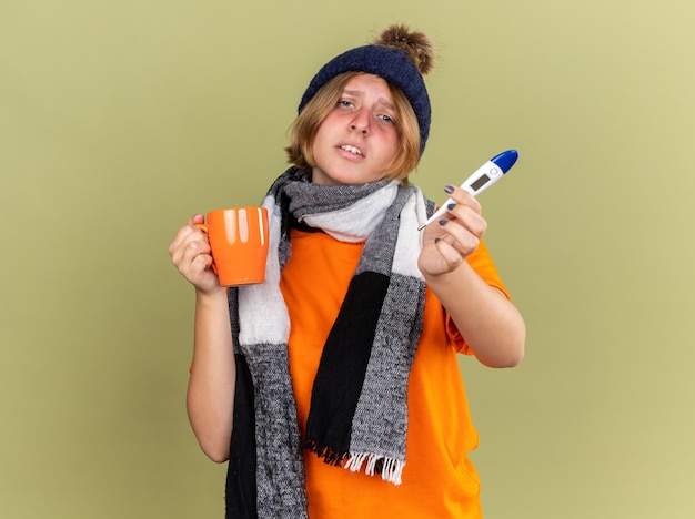 Нездоровая молодая женщина в шляпе с шарфом на шее, чувствуя недомогание, пьет горячий чай с цифровым термометром и страдает от гриппа и лихорадки, стоя над зеленой стеной