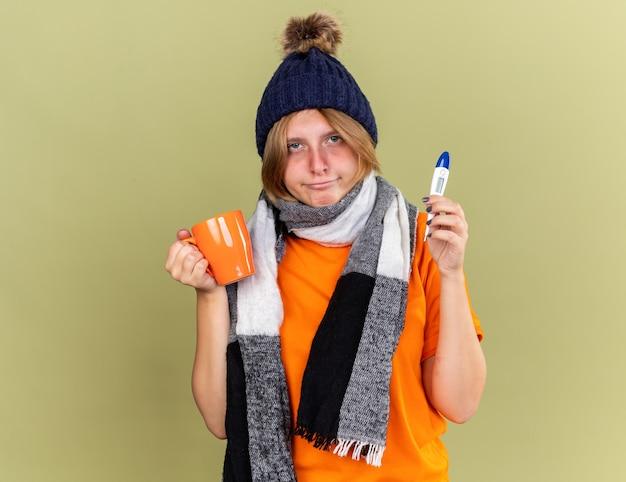 Giovane donna malsana che indossa un cappello con una sciarpa intorno al collo si sente male a bere tè caldo con in mano un termometro digitale che soffre di influenza e febbre