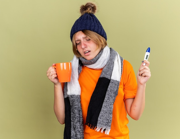 Нездоровая молодая женщина в шляпе с шарфом на шее, чувствуя недомогание, пьет горячий чай с цифровым термометром и страдает от гриппа, стоя над зеленой стеной