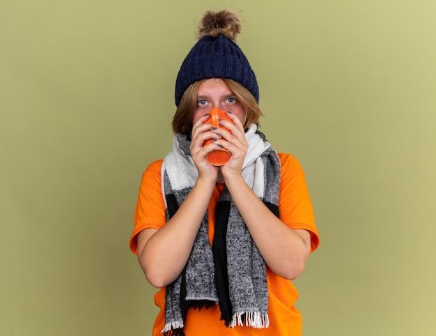 Нездоровая молодая женщина в шляпе с шарфом на шее чувствует недомогание, пьет горячий чай, страдает от простуды и гриппа, стоя у зеленой стены