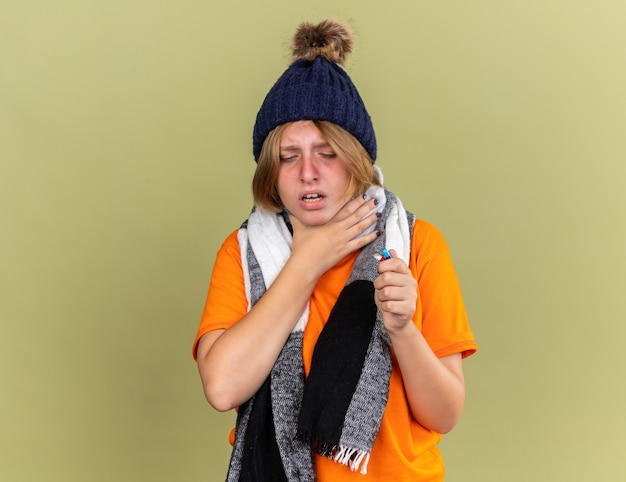 Unhealthy young woman wearing hat with scarf around her neck feeling unwell holding different pills suffering from throat sore touching feeling pain neck standing over green wall