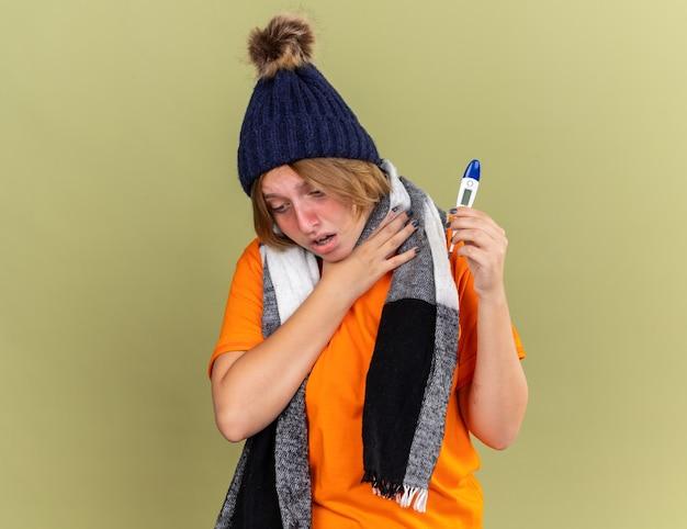 Нездоровая молодая женщина в шляпе с шарфом на шее чувствует себя плохо с цифровым термометром, страдает от гриппа и болит горло, касается ее шеи, стоя над зеленой стеной