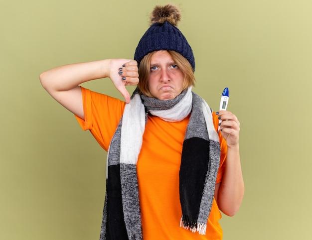 Giovane donna malsana che indossa un cappello con una sciarpa intorno al collo e si sente male tenendo in mano un termometro digitale che soffre di influenza e febbre che mostra i pollici verso il basso in piedi sul muro verde