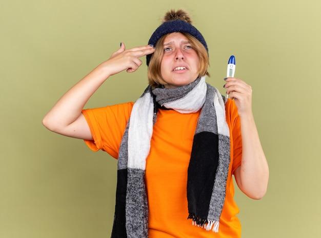 Giovane donna malsana che indossa un cappello con una sciarpa intorno al collo con un termometro digitale che si sente male facendo un gesto di pistola con le dita sulla tempia con febbre