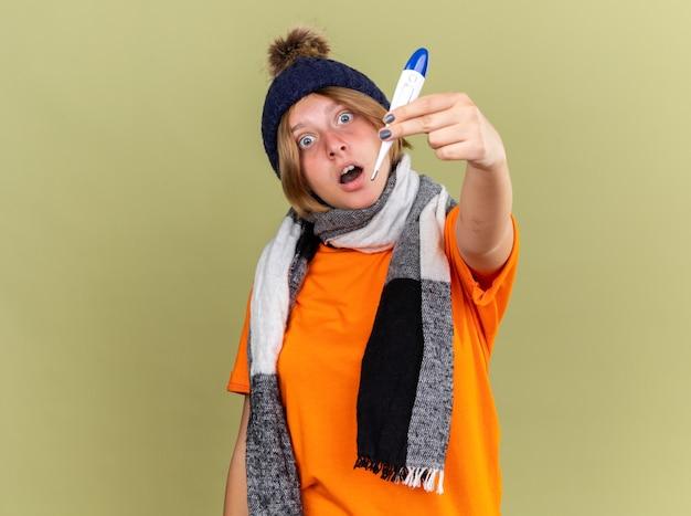 Giovane donna malsana che indossa un cappello con una sciarpa intorno al collo con un termometro digitale che sembra stupito e preoccupato in piedi sul muro verde