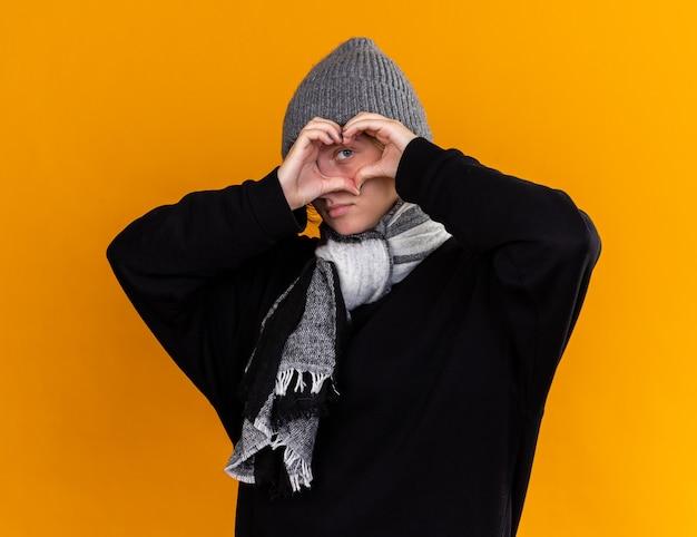 暖かい帽子をかぶって首にスカーフを巻いた不健康な若い女性は、指を通して見ている指で心臓のジェスチャーをより良くするために寒さを感じました