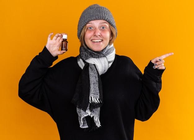 暖かい帽子をかぶり、首にスカーフを巻き、風邪やインフルエンザに苦しんでいる不健康な若い女性が、オレンジ色の壁の上に立って笑顔で薬瓶を持っている