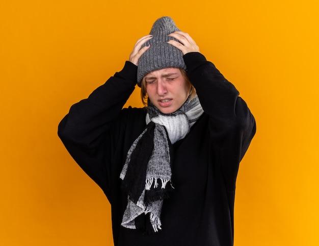 건강에 해로운 젊은 여성이 따뜻한 모자를 쓰고 목에 스카프를 씌우고 감기와 독감으로 발열과 오렌지 벽 위에 서있는 강한 두통으로 고통받습니다.