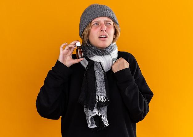 暖かい帽子をかぶって、首にスカーフを巻いて風邪やインフルエンザに苦しんでいる不健康な若い女性は、オレンジ色の壁にイライラした表情で脇を見て薬瓶を持っています