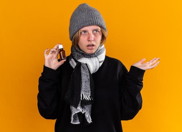 暖かい帽子をかぶり、首にスカーフを巻いて風邪やインフルエンザに苦しんでいる不健康な若い女性が、オレンジ色の壁の上に腕を立てて薬瓶を持っている