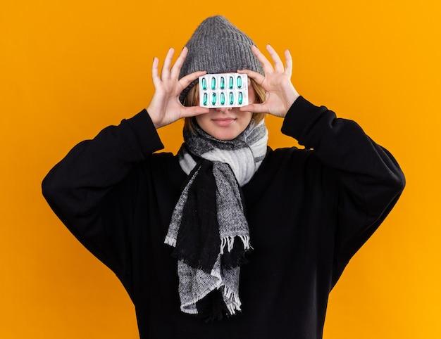 건강에 해로운 젊은 여성이 따뜻한 모자를 쓰고 그녀의 목에 스카프를 낀 채 감기와 독감이 그녀의 눈을 통해 약을 들고 아픈 고통을 느끼고 있습니다.