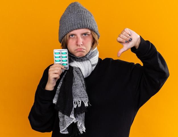 건강에 해로운 젊은 여성이 따뜻한 모자를 쓰고 그녀의 목에 스카프로 감기와 독감으로 고통을 느끼며 찡그린 얼굴로 엄지 손가락을 보여주는 약을 들고 있습니다.