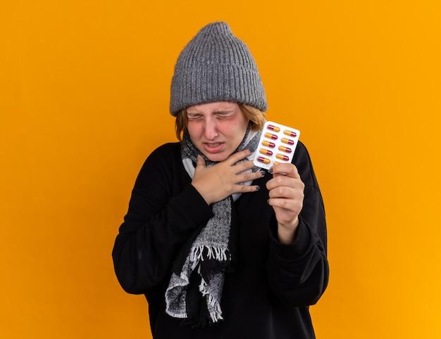 Нездоровая молодая женщина в теплой шляпе и с шарфом на шее чувствует себя больной, страдает простудой и гриппом, держит таблетки и страдает от боли в горле
