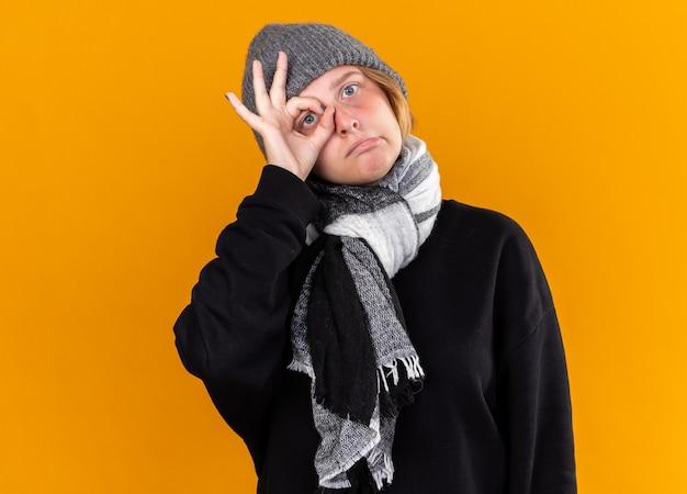 건강에 해로운 젊은 여성이 따뜻한 모자를 쓰고 그녀의 목에 스카프로 감기와 독감으로 고통받는 느낌이 들며 손가락으로 ok 사인을 만드는 혼란스러워 보입니다.